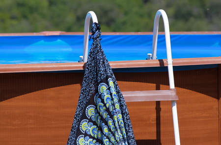 Pool ladder with hanging colored sarongs.