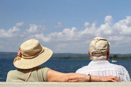 Elderly couple sitting on a bench by the lake.