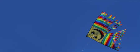 Big colorful kite silhouetted against the blue sky, copy space.