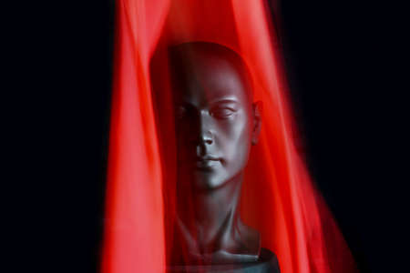 3d Illustration. Black plastic mannequin head with large red silk scarf, blur effect, black background.