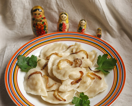 ukranian: Russian vareniki with potato and fried onion with matreshkas on the background