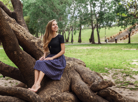 conection: Beautiful caucasian girl sitting on the tree in the park and smiling. Nature conection concept.