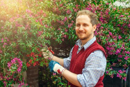 Sonriente hombre caucásico que trabaja en el jardín soleado día de primavera.