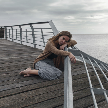 melancholy: Beautiful sad girl sitting on the old berth at the sea cloudy day. Melancholy. Stock Photo