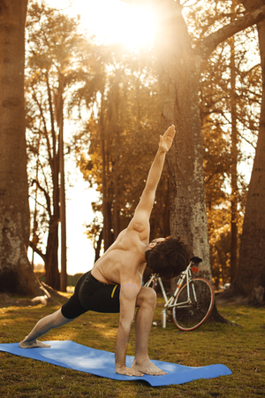 exersice: Young man doing yoga in the mornig autumn forest. Lifestyle.  Stock Photo