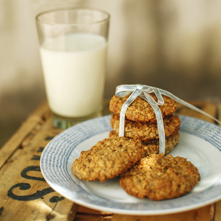 Homemade organic oatmeal and banana cookies with glass of milk on the wooden background. Selective focus.