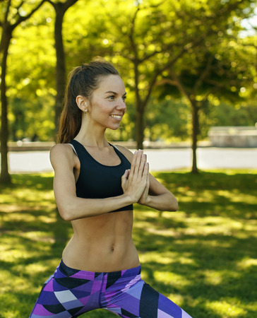 Portrait of beautiful caucasian girl doing yoga outdoors on nature background holding hands in namaste. Harmony, healthy lifestyle.
