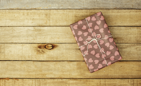 Wooden background with gift in vintage wrap. Lovely present. Christmas. Saint Valentine. Copy space.