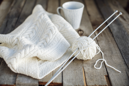 ovine: Beautiful white knitted scarf and ball of wool with needles and cup of tea on old wooden table. Cozy winter. Hobbies. Selective focus.  Stock Photo