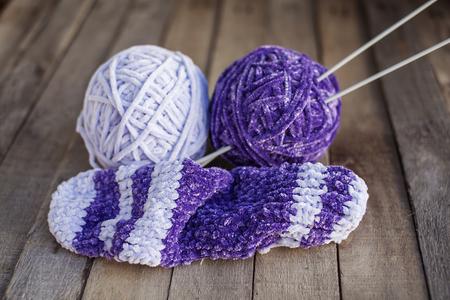 tejido de lana: Tejer: dos bolas de hermoso hilo violeta con agujas sobre fondo de madera. Aficiones. Enfoque selectivo.