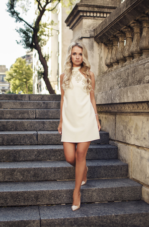 Attractive blonde girl in white dress going down stairs outdoors in beautiful old city. Stock Photo