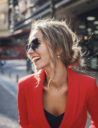 Portrait of happy beautiful fashionable woman in red suit and sunglasses laughing outdoors, emotion  Фото со стока