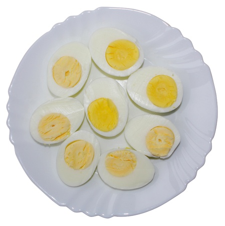 Hard boiled eggs sliced in half, in a plate isolated on white background photo
