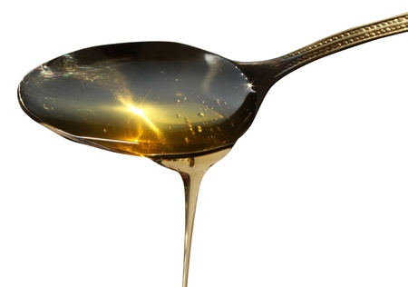 Honey dripping from a spoon, isolated on a white background Stock Photo