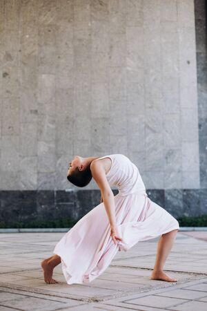 Authentic girl dances on the street barefoot in a white T-shirt and a long flying pink skirt. Girl is short-haired.