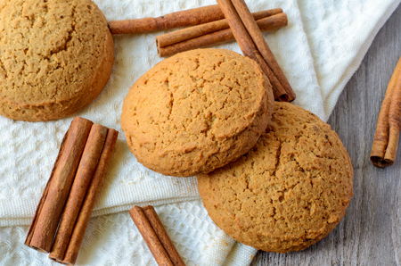 oatmeal cookie: Oatmeal cookies and cinnamon sticks on white background Stock Photo