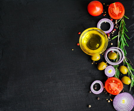 greece granite: Top view of olive oil and ingredients for a healthy vegetarian salad - cherry tomatoes, olives, garlic and rosemary on natural black slate background with copy space for your text