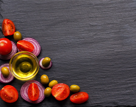 greece granite: Banner top view on olive oil and ingredients for a healthy salad with cherry tomatoes, onion and olives on natural black slate background with copy space for your text