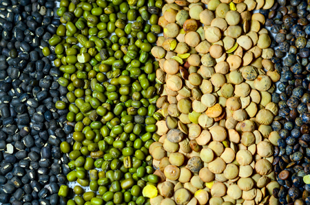 black gram: Top view of lentils and mung beans, green and black, on natural kitchen linen background