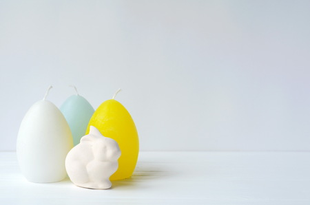 Easter (Ostara, Eoster) bunny with egg shaped candles on white background with copy space