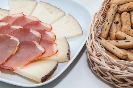 gressins: Assiette de fromage et longe de porc et de bâtons dans un panier