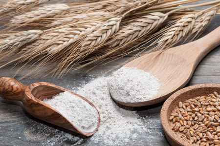 wheat: Flour in a wooden spoon and wheat grains Stock Photo
