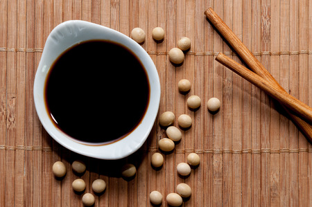 soy sauce: A bowl of soy sauce, soy grains and chopsticks
