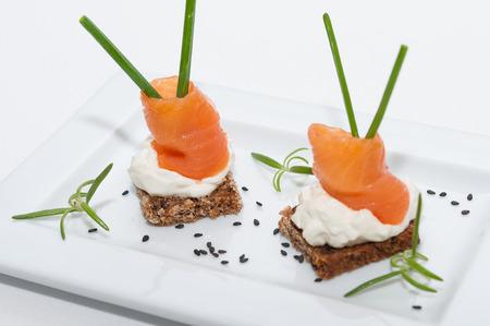 salmon ahumado: Placa con dos canapés de salmón ahumado con queso crema