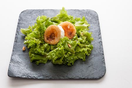 pinoli: Insalata di lattuga, formaggio di capra, uva passa e pinoli Archivio Fotografico