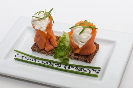 salmon ahumado: Placa con dos canapés de salmón ahumado con queso