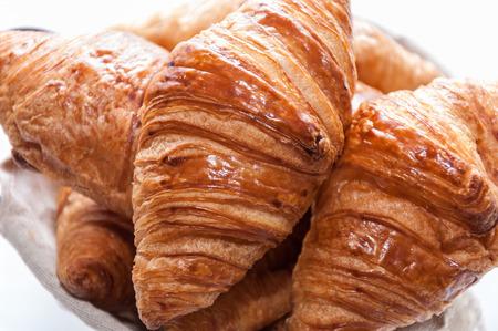 croissant: A few crispy croissant piled in a basket