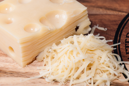 emmental: Grated Emmental cheese on a wooden board Stock Photo