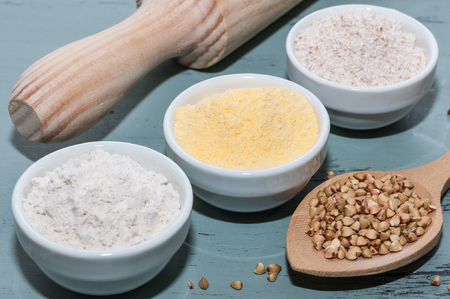 Three white bowls with corn flour and buckwheat and utensils Stock Photo