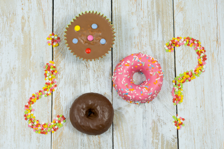 Composition made with muffin, donuts and sugar stars as question marks