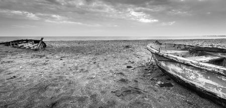 Two wooden boats abandoned and worn by the passage of time, in black and white, on a beach of Almeria, Spain. Stock Photo