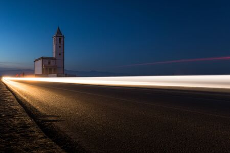 Wake of light from a car and in the background the Church of Las Salinas located in Cabo de Gata, Almeria. Long exposition.