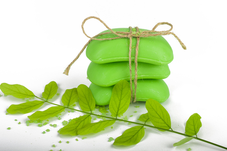 Green soap, tied with twine, bath salt. Sprig with leaves. On white, isolated background. Reklamní fotografie