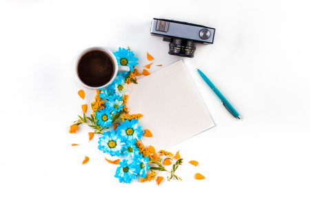 White cup with handle kofe.Sinyaya. Silver with black camera. Square light a piece of paper. Blue and orange flowers are a month on a light background. Top view. Flat lay. Stock Photo