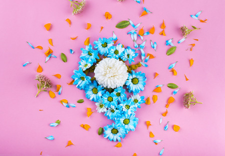 The composition of the blue and beige colors. Blue and orange petals. Green branches and leaves. on a pink background. Top view. Flat lay.