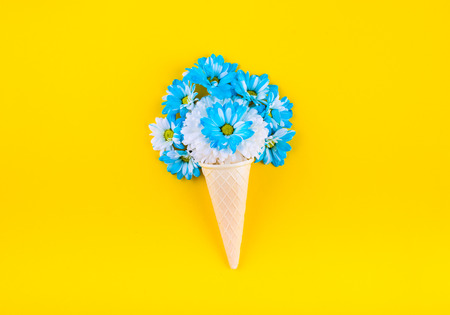 Waffle ice cream cone out of the blue and beige colors. On a yellow background. Top view. Flat lay.