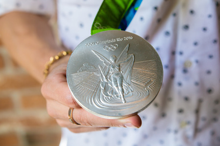 olympic games: MOSCOW, RUSSIA - AUGUST 26, 2016: Meeting with the russian gymnast David Belyavskiy.Silver and bronze medals of Olympic Games in Rio demonstration. Silver medals obverse.