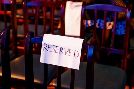 reserved seat: One wooden theater seat with the handwritten reserved sign. Color light.