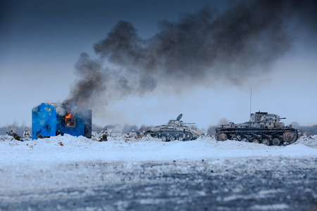 Winter view of the german tanks (panzers) in the attack with burning house. Reconstruction of the winter defensive battles of the Red Army in WWII (1944 year). Stock Photo