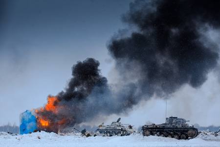 Winter view of the german tanks (panzers) with burning house in the battle. Reconstruction of the winter defensive battles of the Red Army in WWII (1944 year). Stock Photo
