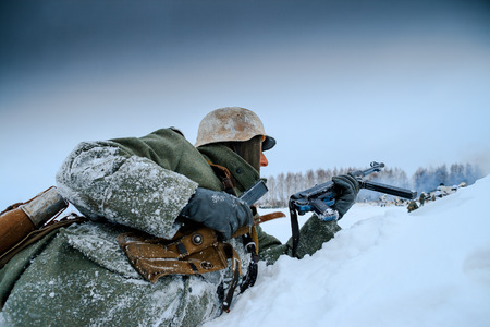 German Wehrmacht Soldier is reloading his submachine gun. Reconstruction of the winter defensive battles of the Red Army in WWII (1944 year).