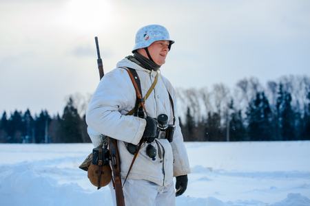 NELIDOVO, MOSCOW REGION, RUSSIA - JANUARY 22, 2017: Reconstruction of the winter defensive battles of the Red Army of the 1st Ukrainian Front in WWII called Battlefield. Hot snow (1944 year). German Wehrmacht infantryman.