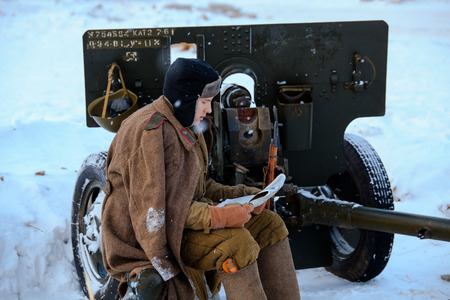 NELIDOVO, MOSCOW REGION, RUSSIA - JANUARY 22, 2017: Reconstruction of the winter defensive battles of the Red Army of the 1st Ukrainian Front in WWII called Battlefield. Hot snow (1944 year). Red army soldier is reading the newspaper sitting on the 76-m