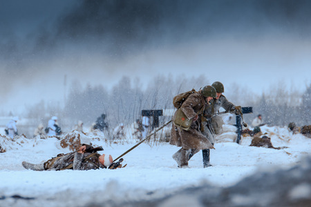 wehrmacht: NELIDOVO, MOSCOW REGION, RUSSIA - JANUARY 22, 2017: Reconstruction of the winter defensive battles of the Red Army of the 1st Ukrainian Front in WWII called Battlefield. Hot snow (1944 year). Red Army medics in action with the injured soldier in the bat Editorial