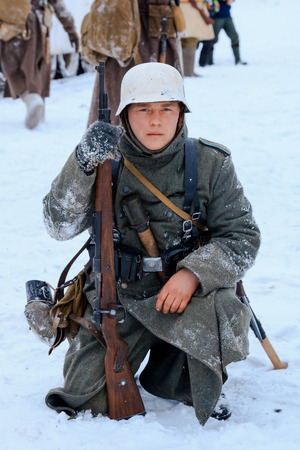 NELIDOVO, MOSCOW REGION, RUSSIA - JANUARY 22, 2017: Reconstruction of the winter defensive battles of the Red Army of the 1st Ukrainian Front in WWII called Battlefield. Hot snow (1944 year). Wehrmacht soldier after battle. Editorial