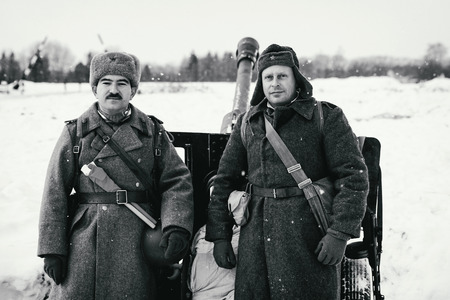 wehrmacht: NELIDOVO, MOSCOW REGION, RUSSIA - JANUARY 22, 2017: Reconstruction of the winter defensive battles of the Red Army of the 1st Ukrainian Front in WWII called Battlefield. Hot snow (1944 year). Two Red Army cannoneers near the 76-mm divisional gun M1942 (